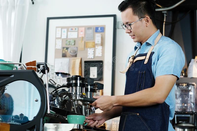 Young asian man barista making a cooffe cup at counter cafe back royalty free stock photography