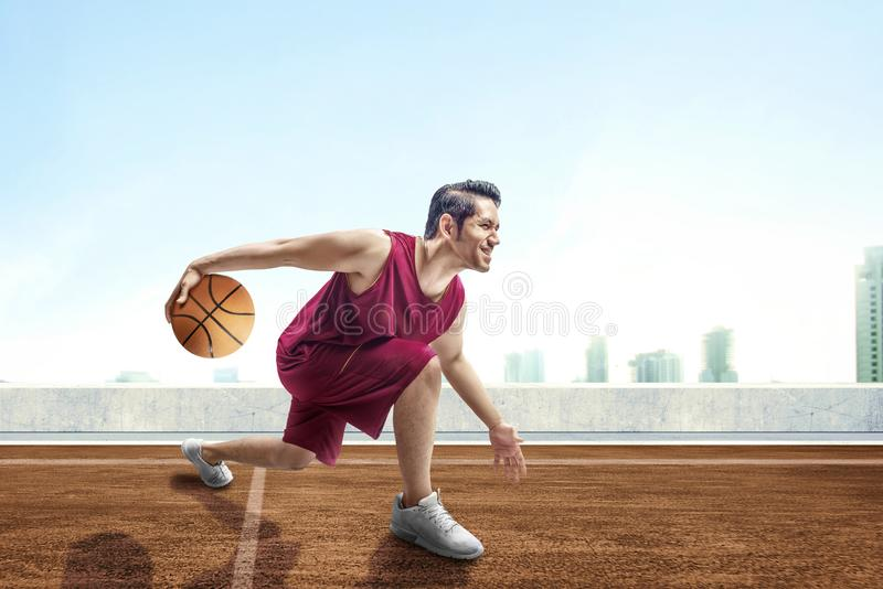 Young asian man basketball player posing in dribbling the ball between the legs on outdoor basketball court. With cityscapes and blue sky background royalty free stock photos