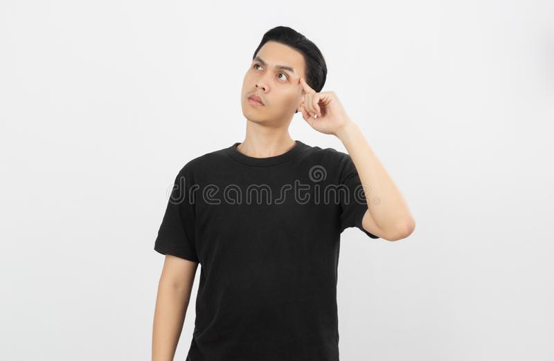 Young asian man with black shirt having doubts and with confuse face expression while scratching head on isolated on white. stock photos