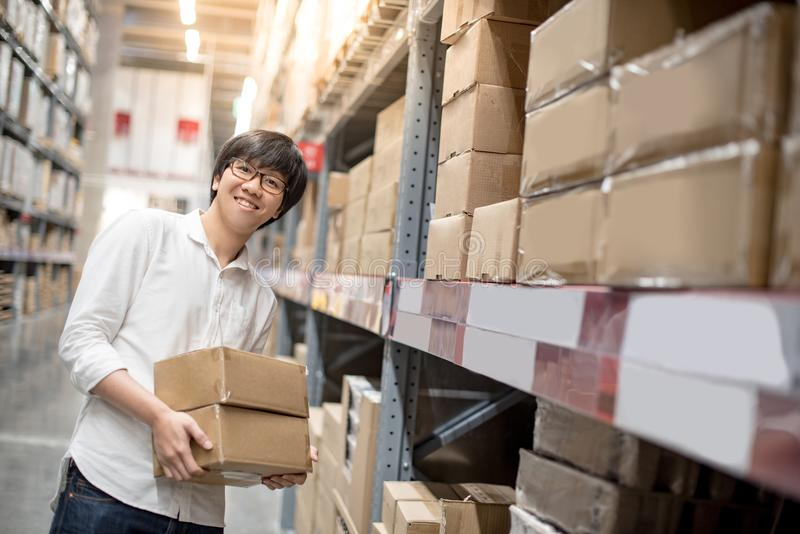 Young Asian man carrying paper boxes in warehouse stock photos