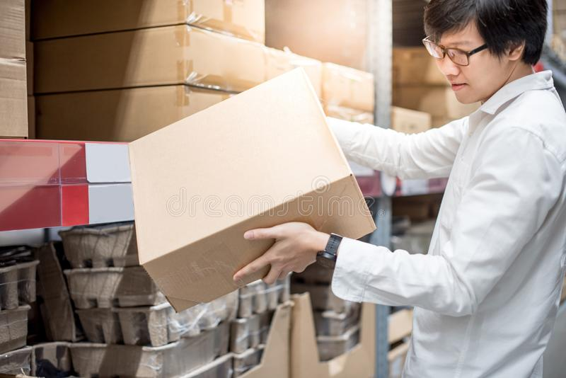 Young Asian man carrying paper boxes in warehouse stock photo