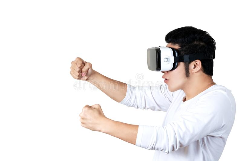 Young asian man in casual outfit holding or wearing VR glasses goggles playing car racing video game, shocked and amazed on white royalty free stock photos