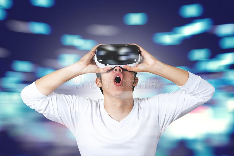 Young asian man in casual white wearing and holding VR glasses by hands looking up above feeling excited and amazed royalty free stock image