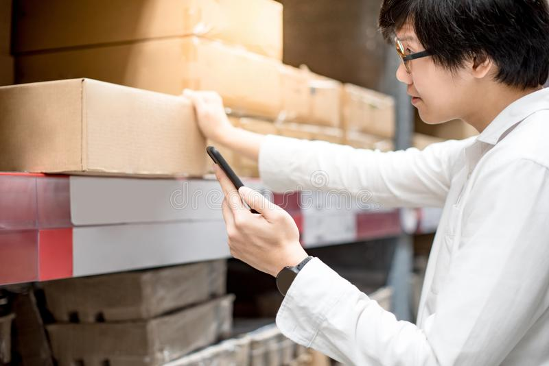 Young Asian man checking shopping list from smartphone in warehouse. Young Asian man checking the shopping list on his smartphone near product shelf. warehouse stock photo