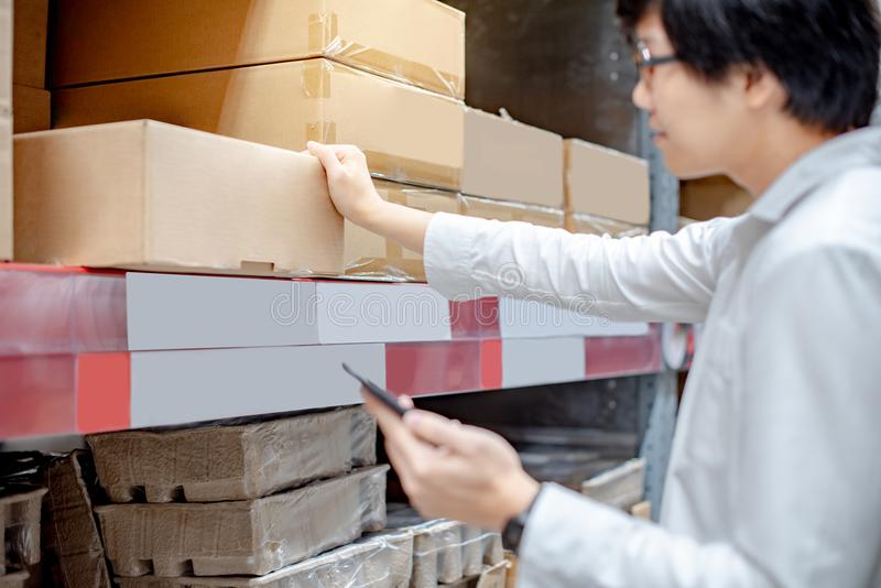 Asian man checking shopping list from smartphone in warehouse. Young Asian man checking the shopping list on his smartphone at product shelves. Warehouse stock images