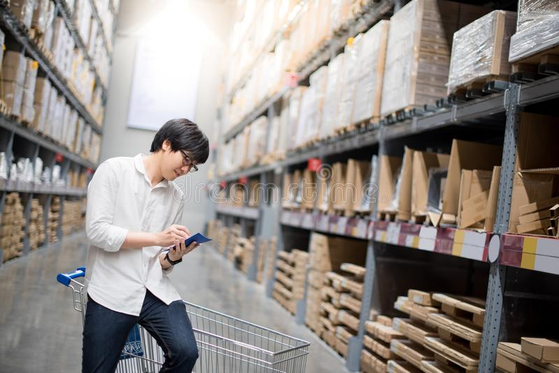 Young Asian man checking the shopping list in warehouse. Young Asian man standing with cart checking the shopping list and looking for product in warehouse royalty free stock images