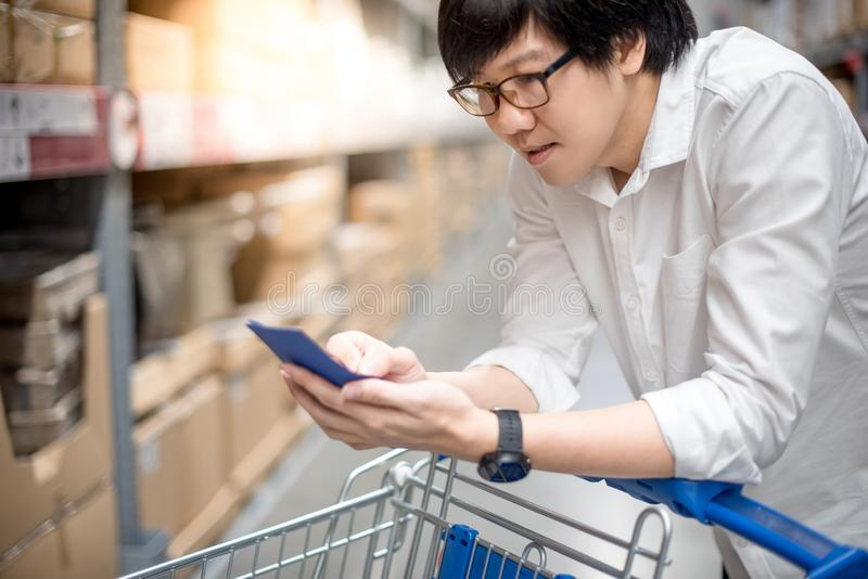 Young Asian man checking the shopping list in warehouse. Young Asian man standing with cart checking the shopping list in warehouse wholesale, shopping stock photography