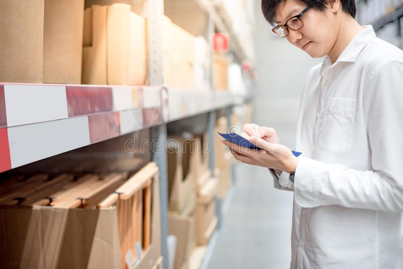 Young Asian man checking the shopping list in warehouse. Young Asian man standing checking the shopping list and looking for product in warehouse wholesale royalty free stock photo