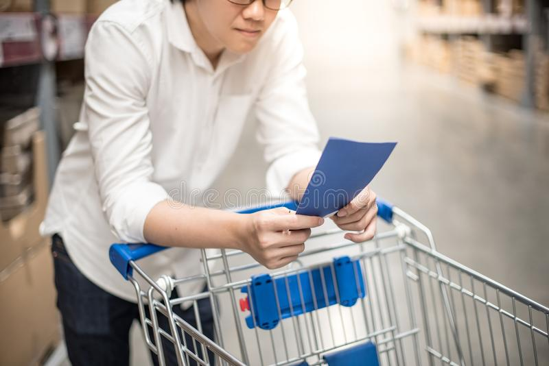 Young Asian man checking the shopping list in warehouse. Young Asian man standing with cart checking the shopping list in warehouse wholesale, shopping royalty free stock photography