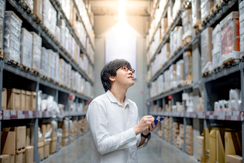 Young Asian man checking the shopping list in warehouse. Young Asian man standing checking the shopping list and looking for product in warehouse wholesale royalty free stock images