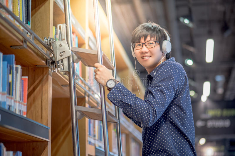 Young Asian man choosing book using ladder in library stock photo