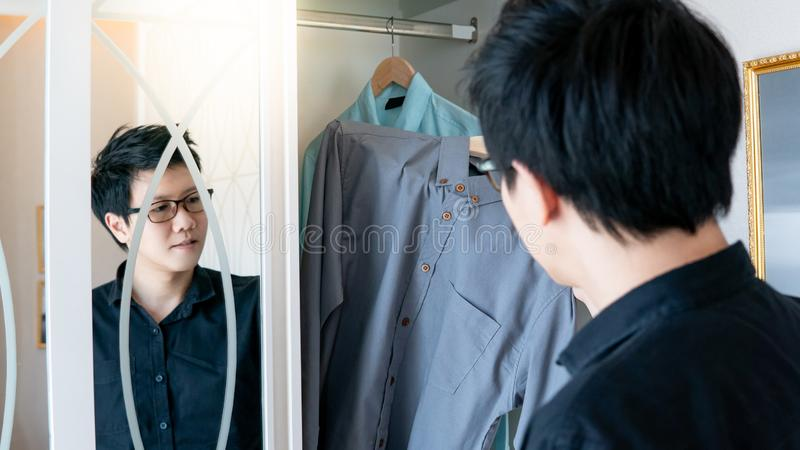 Asian man choosing shirt in closet. Young Asian man choosing casual style shirt in closet for dressing up in the bedroom. Home living lifestyle concept royalty free stock photos