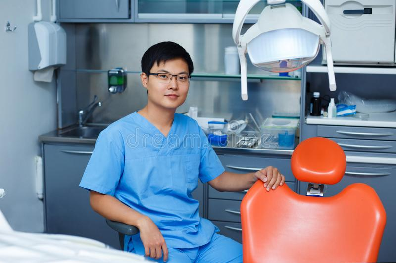 Young asian man dentist with dentist chair at the clinic. Dentis stock image