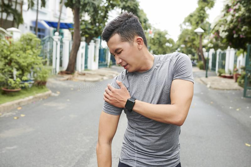 Sportsman dislocated shoulder. Young Asian man dislocated shoulder when training outdoors royalty free stock image