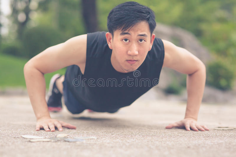 Young Asian Man doing push ups outdoor. royalty free stock image