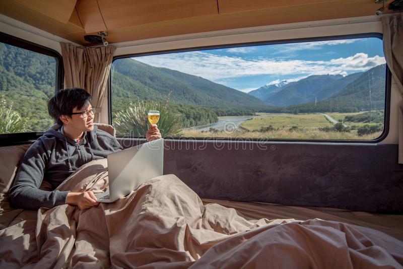 Young Asian man drinking beer and working with laptop in camper stock images