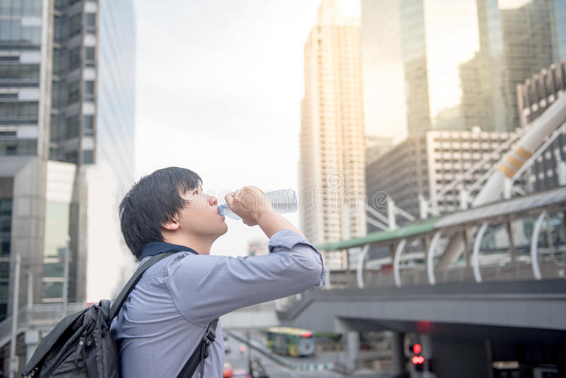 Young Asian man drinking a bottle of water. In the city, urban healthy lifestyle concepts royalty free stock photo