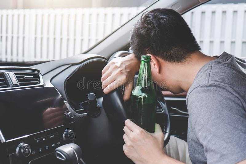 Young asian man drives a car with drunk a bottle of beer and fall asleep behind the wheel of a car stock images