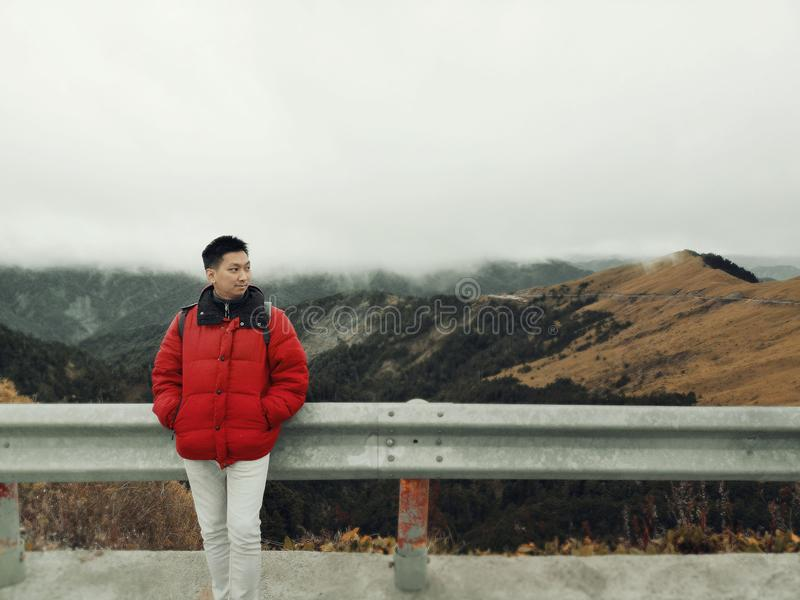 Young Asian Man Enjoying in the Wind and Mist on Mountain Top with Beautiful Landscape in Background royalty free stock images