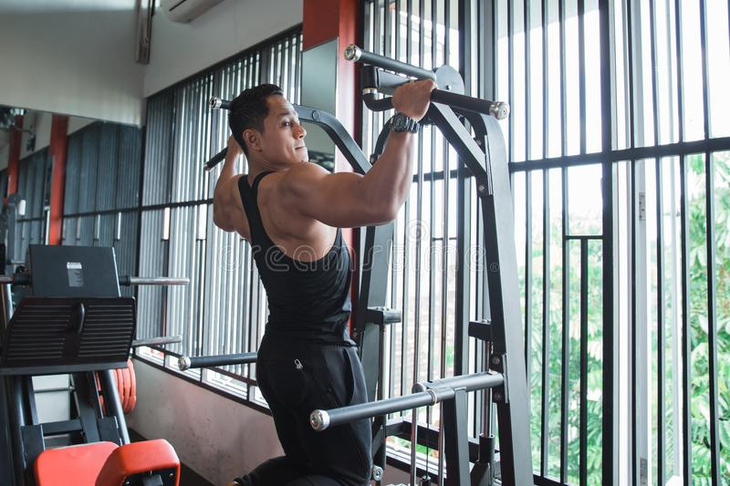 Young asian man exercising and doing pull ups stock photo