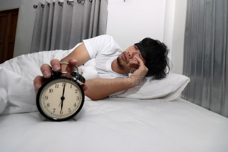 Young Asian man with eye mask wake up and stop alarm clock on the bed royalty free stock photography