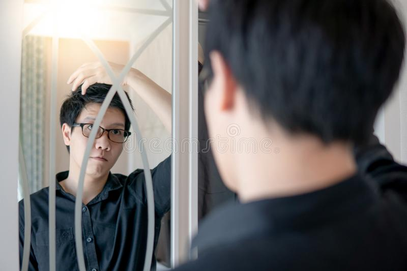 Asian man looking into the mirror on closet. Young Asian man with glasses looking into the mirror on closet while dressing up in bedroom. Home living concept stock photo