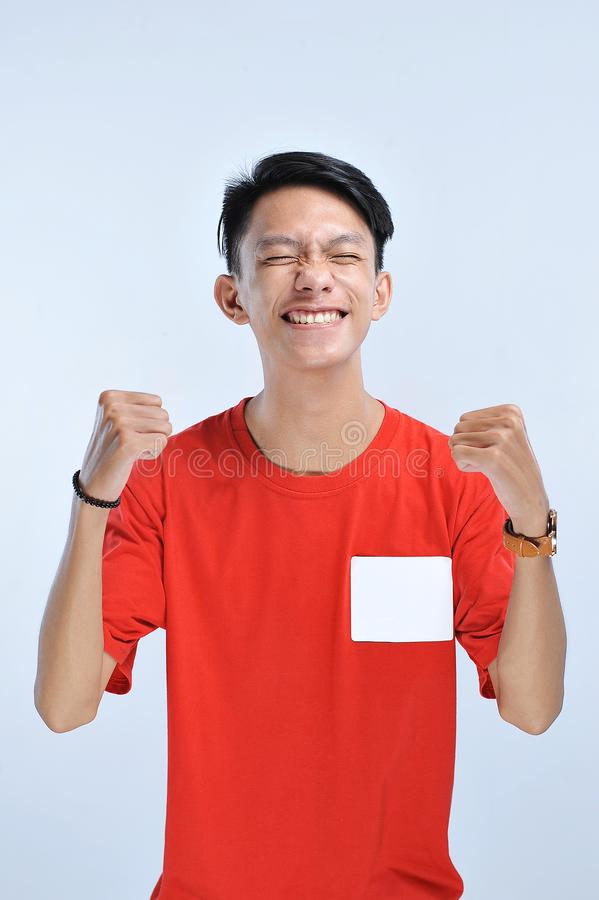 Young asian man happy and excited expressing winning gesture. Successful and celebrating royalty free stock photography
