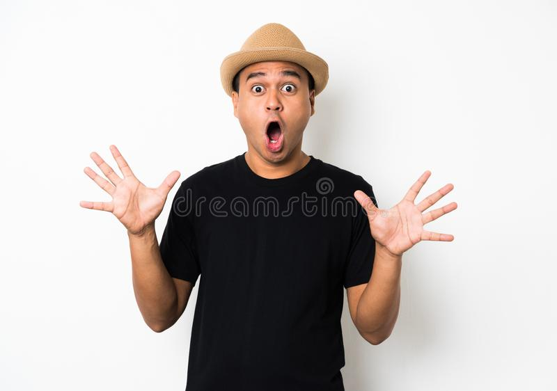 Young Asian man with hat feels shock and surprise with overly face expression. royalty free stock image