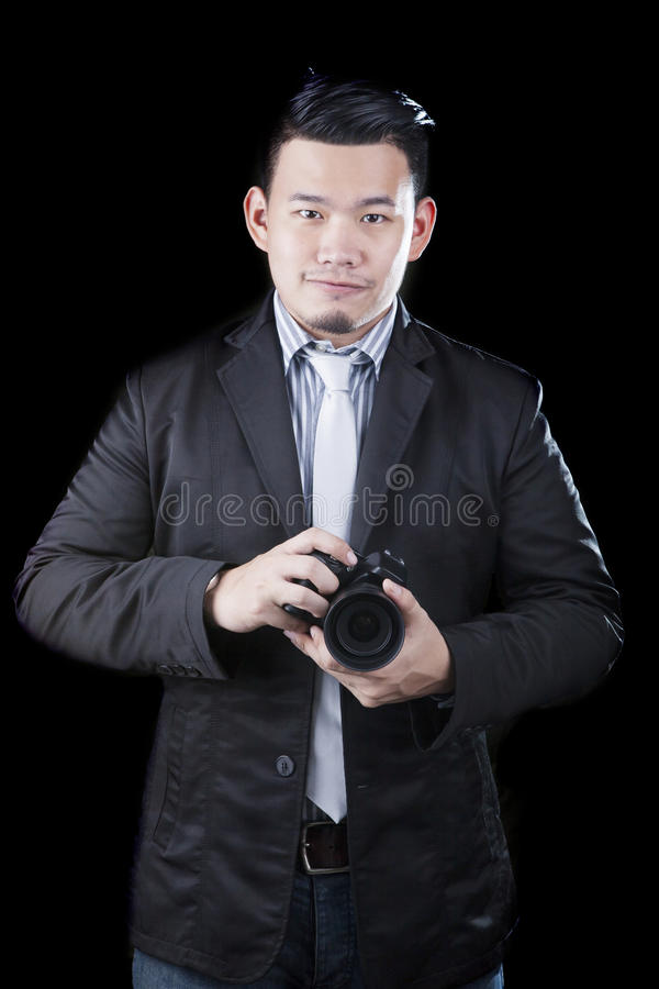 Young asian man holding dslr camera take a photography by low key ,low light white dark background technical use for people. Activities and human occupation stock photos
