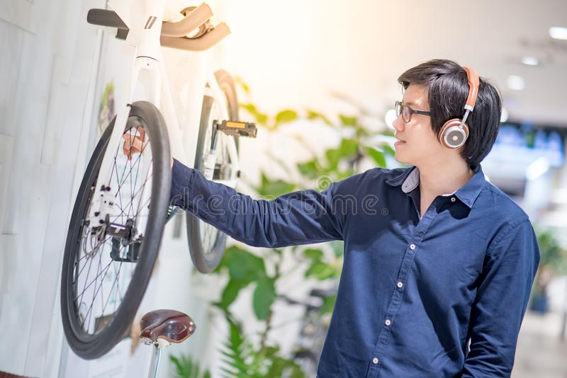 Young Asian man looking for bicycle in bike shop. Young Asian man with headphones and glasses looking for bicycle at bike shop in department store, urban royalty free stock image