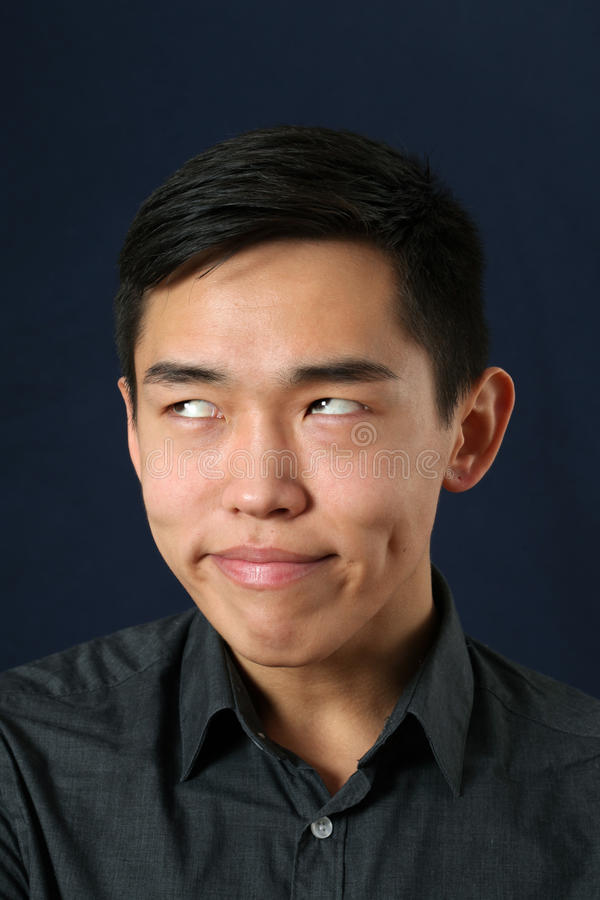 young asian man making face and rolling eyes up stock