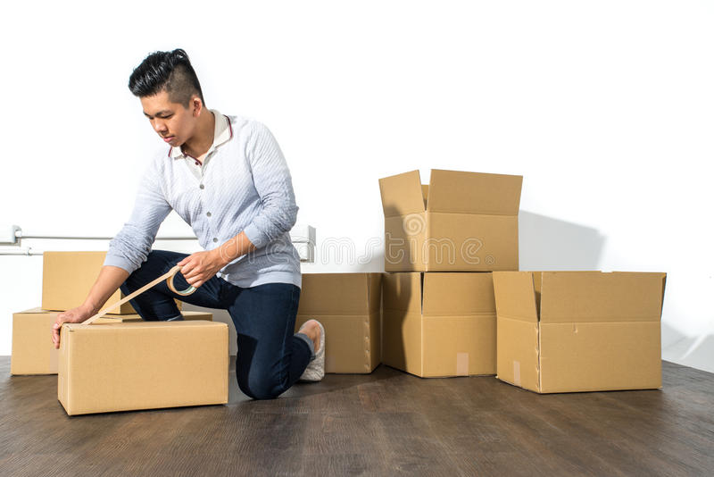 Young asian man moving house Packing cardboard using adhesive stock photos