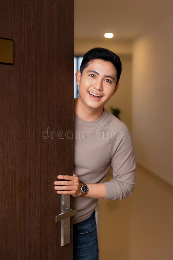 Young asian man open his front house door and smiling royalty free stock image