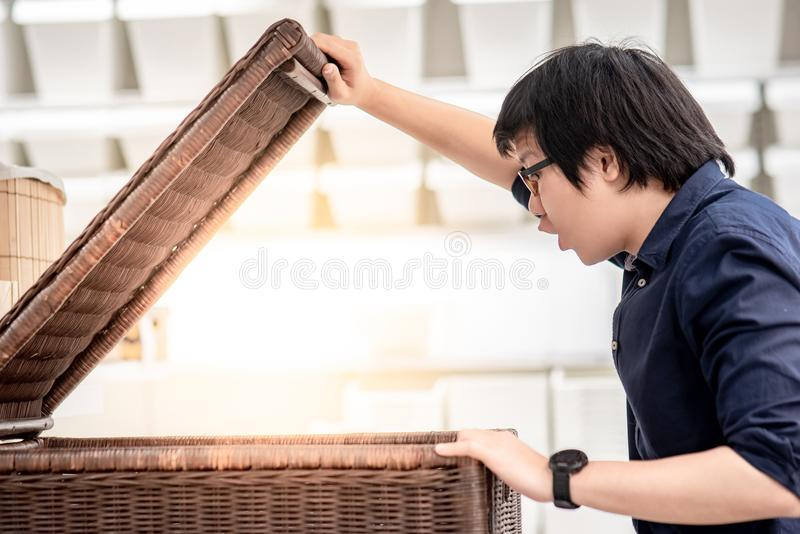 Young Asian man opening wooden box looking inside. Young Asian man opening a big woven wooden box looking inside. Home decoration concept stock photo