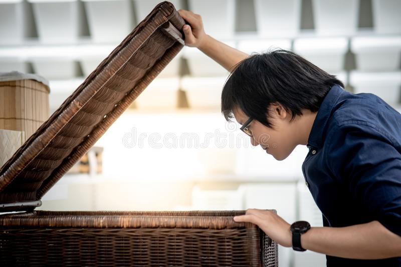 Young Asian man opening wooden box looking inside. Young Asian man opening a big woven wooden box looking inside. Home decoration concept royalty free stock images