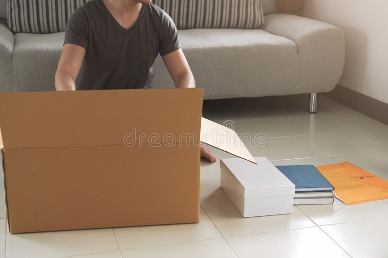 Young asian man packing and putting stuff in big cardboard box f royalty free stock photo