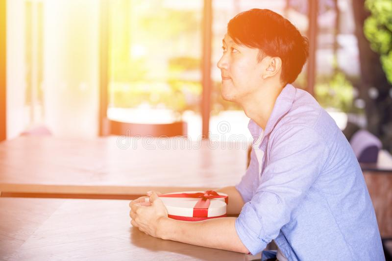 Young Asian man patiently sitting in cafe restaurant and holding a present gift giving to someone special for special occasion. stock photography
