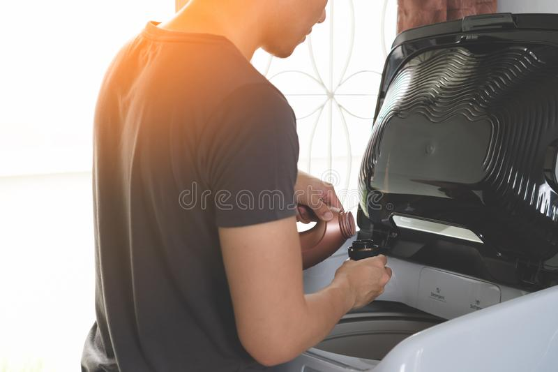 Young asian man pouring liquid laundry detergent and softener in royalty free stock photography