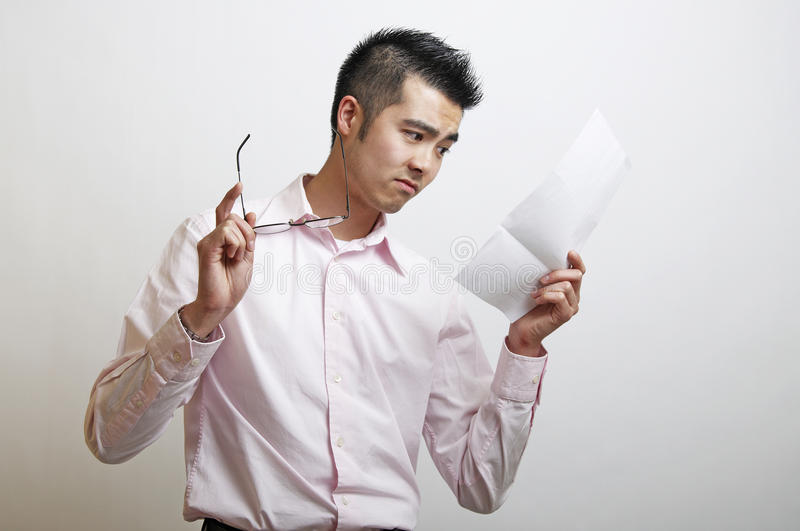 Download A Young Asian Man Reading A Letter Stock Image - Image of disturbing, standing: 13727591