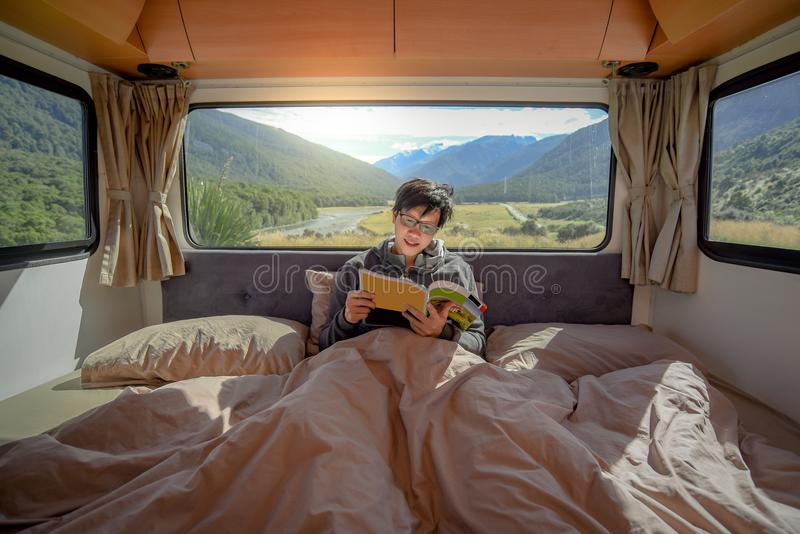 Young Asian man reading magazine book in camper van royalty free stock images