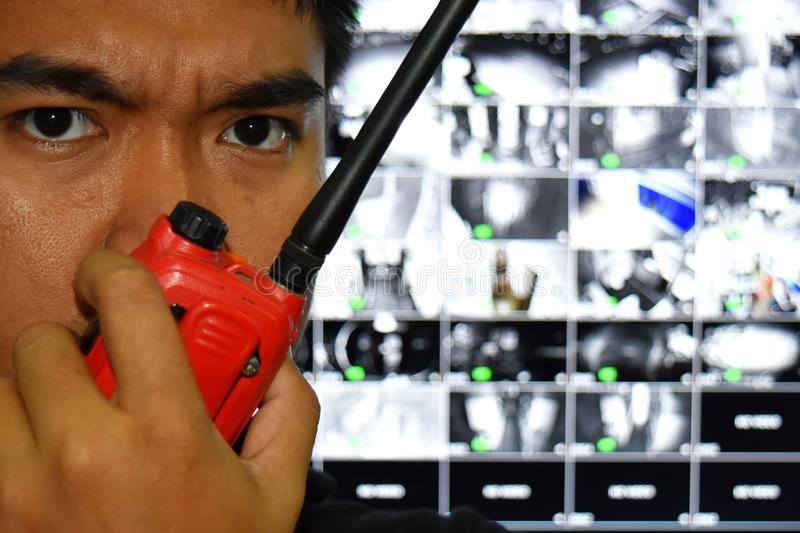 Young asian man and red radio communicationblurred many channel all in one cctv monitor in secret office stock photography