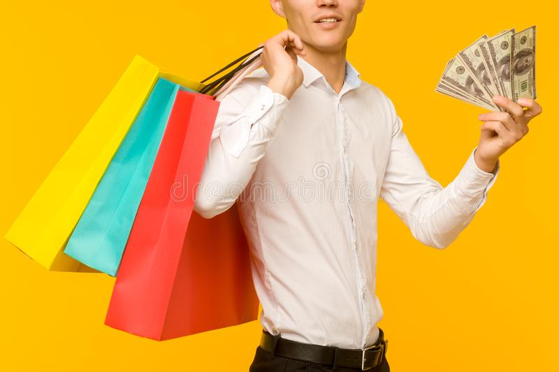 Young asian man showing his shopping bag and money royalty free stock photo
