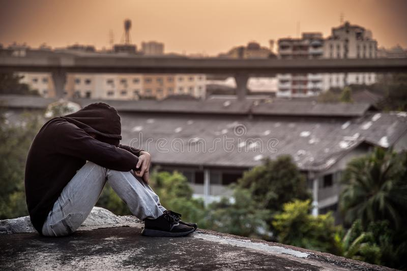 Young Asian man sitting rooftop of building with depression stress out stock photos