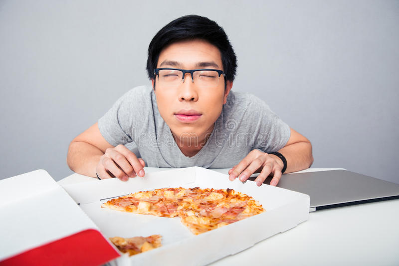Young asian man smelling pizza stock photography
