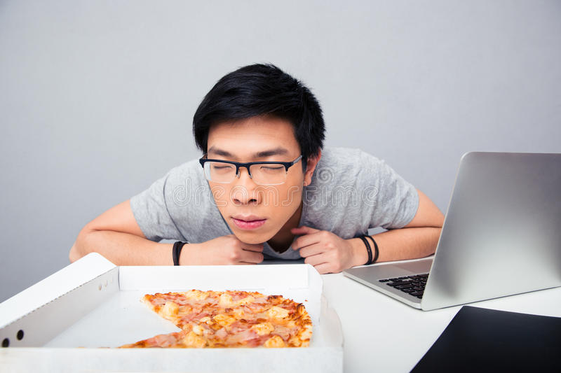 Young asian man smelling pizza royalty free stock photos