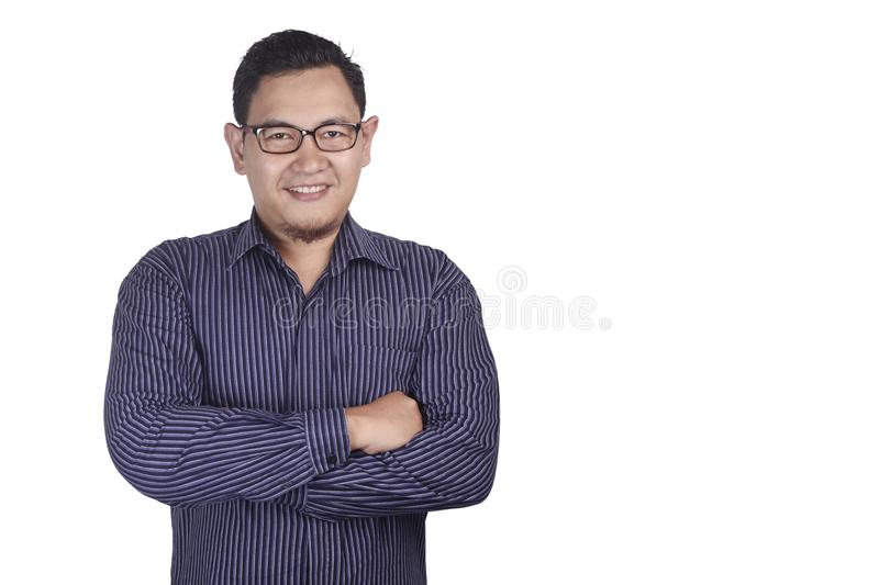 Young Asian Man Smiling Happily. Photo image portrait of funny young attractive cute Asian man smiling happily, with arms crossed adult casual cheerful stock photo