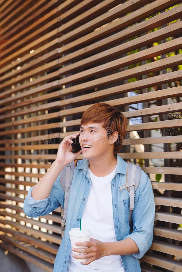 Young asian man smiling and talking on mobile phone outside with copy space on the left stock photos