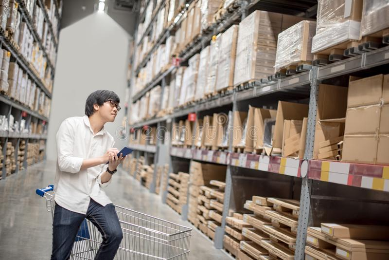 Young Asian man checking the shopping list in warehouse. Young Asian man standing with cart checking the shopping list and looking for product in warehouse stock photo
