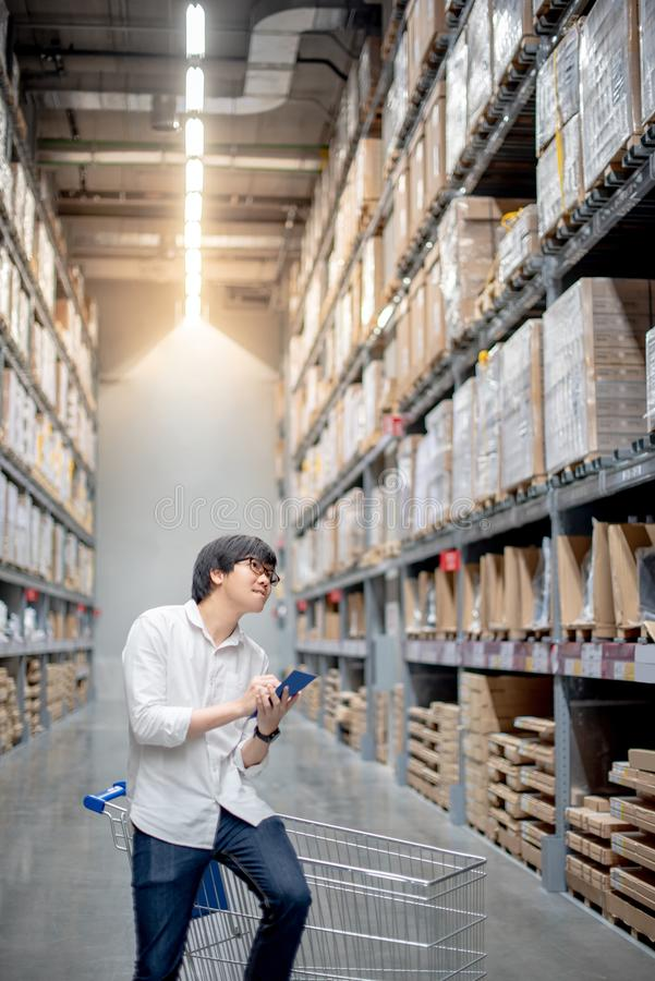 Young Asian man checking the shopping list in warehouse. Young Asian man standing with cart checking the shopping list and looking for product in warehouse royalty free stock photo