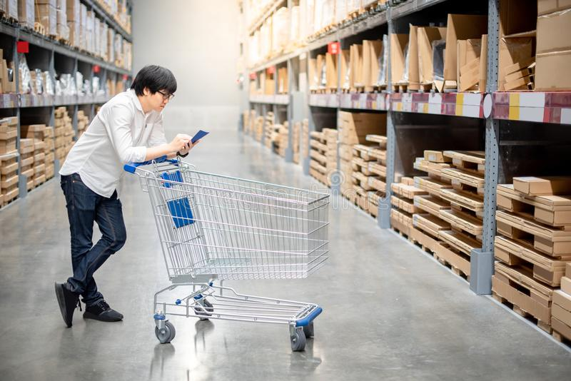 Young Asian man checking the shopping list in warehouse. Young Asian man standing with cart checking the shopping list and looking for product in warehouse stock photography